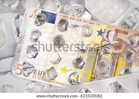 Banknote 50 euro on an empty blister pack of tablets - stock photo