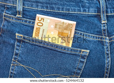 Banknote 50 euro sticking out of the blue jeans pocket. Money for travel and shopping