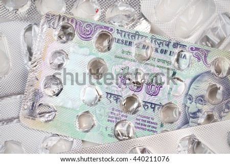 Banknote 100 Indian rupees on an empty blister pack of tablets - stock photo