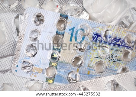 Banknote 10 Tunisian dinars on an empty blister pack of tablets - stock photo