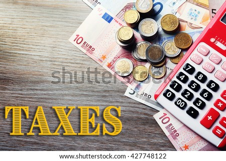 Banknotes and coins on wooden table.Taxes concept - stock photo