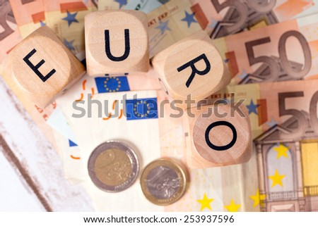 Banknotes and wood dice with the word euro / Euro Money - stock photo