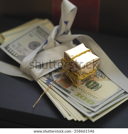 Banknotes as a gift with box wrapped in golden paper on top, concept of success, closeup angled shot - stock photo