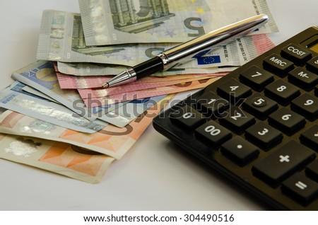 banknotes,coins, calculator and pen - stock photo