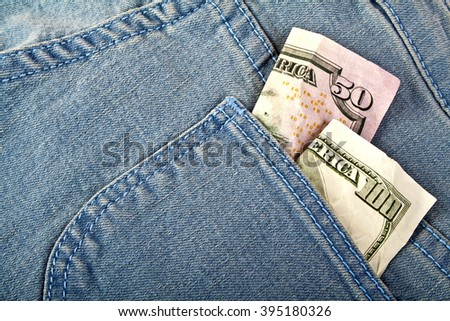 Banknotes of american dollars in jeans pocket - stock photo