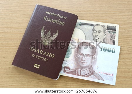 Banknotes of Japan and Thailand in thai passport. - stock photo