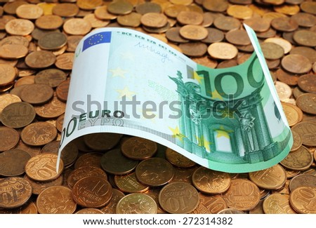 Banknotes of one hundred euros on coins - stock photo