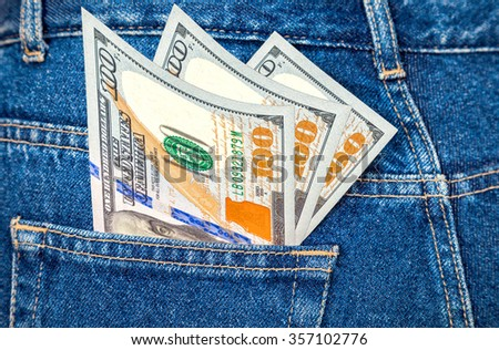 Banknotes of one hundred U. S. dollars bill sticking out of the back jeans pocket - stock photo