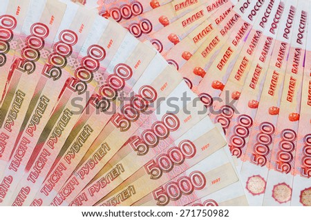 Banknotes of 5000 Russian rubles are located around as two fans as a background. - stock photo