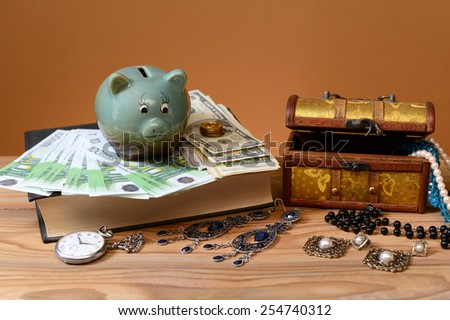 Banknotes, piggy banks and jewelry in a box - stock photo