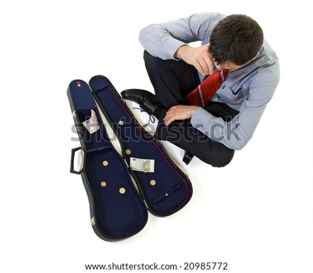 Bankrupt businessman sitting by a violin case with some change - isolated - stock photo