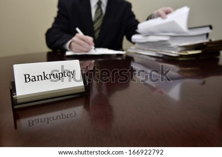 Bankruptcy attorney or accountant sitting at desk with files and papers - stock photo