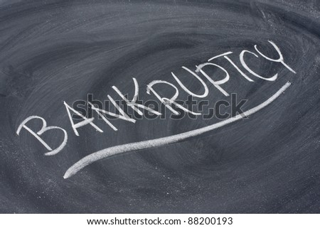 bankruptcy word in white chalk handwriting on blackboard