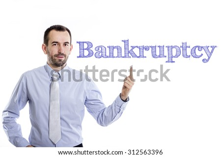 Bankruptcy - Young businessman with small beard pointing up in blue shirt - stock photo