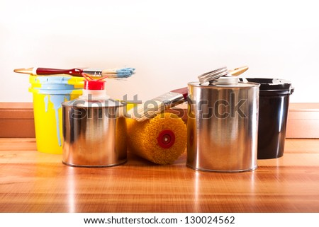 Banks with paints and solvents, brushes and roller on the floor from the parquet - stock photo