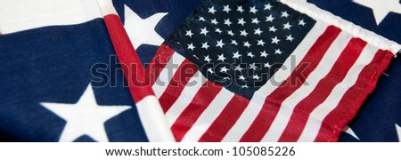 Banner Image of a Miniature United States flag on larger flag - stock photo