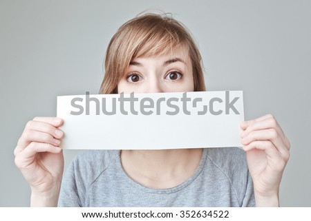 Banner sign woman peeking over edge of white blank empty paper billboard with copy space for text. Beautiful Caucasian woman looking surprised  Isolated on white background. - stock photo