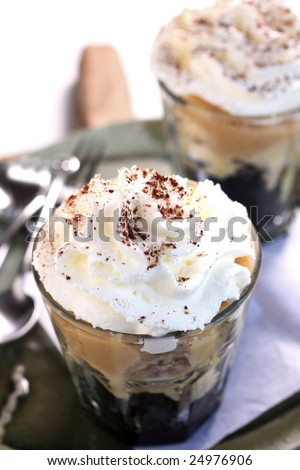 banoffee oreo pie in a cup, spilled with caramel and whipped cream, delicious dessert.