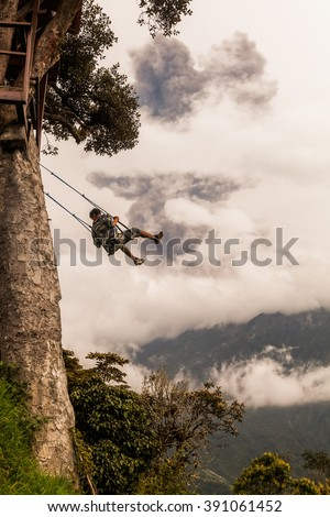 Banos De Agua Santa, Ecuador- March 08, 2016: Happy Adult Caucasian Man Swinging On A Swing, Tungurahua Volcano Explosion In The Background, South America