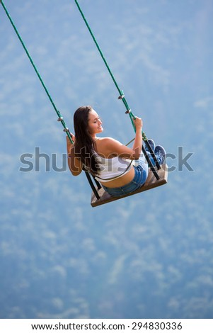 BANOS, ECUADOR - FEB 21: Unidentified young woman swinging at the La casa del Arbol in Banos, Ecuador 2015.