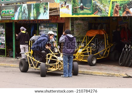 BANOS, ECUADOR - FEBRUARY 25, 2014: Unidentified people in and at a buggy in front of a tour operator and vehicle rental on 16 de Diciembre Street on February 25, 2014 in Banos, Ecuador.  - stock photo