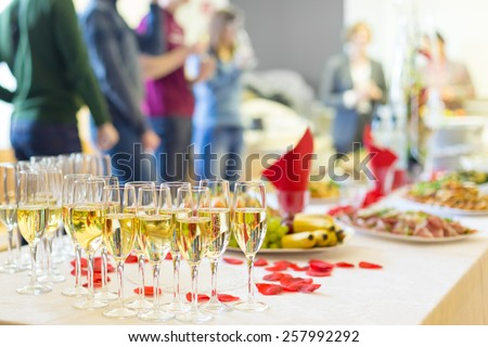 Banquet event. Table with the wineglasses, snacks and cocktails. People celebrating in the background.