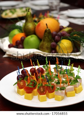 Banquet table. Canape (cheese, tomato, bacon, grapes) and fruit basket with apple, orange, grapes on a background (focus on canape). - stock photo