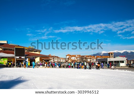 Bansko, Bulgaria - February 19, 2015: Bansko ski station, cable car lift and people waiting in line near it in Bansko, Bulgaria. Snow mountain peaks and blue sky at the background - stock photo
