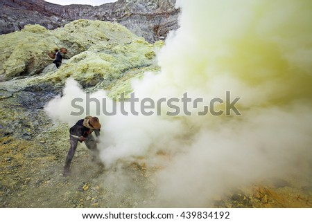 BANYUWANGI, INDONESIA - OCTOBER 27, 2014: Unidentified Sulfur miners inside crater Ijen volcano crater, Banyuwangi district, Indonesia. - stock photo