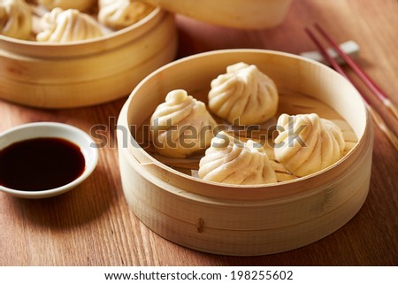 Baozi chinese dumplings on bamboo steamer - stock photo
