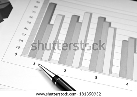 Bar charts and pen as accounting or business concept in black and white - stock photo
