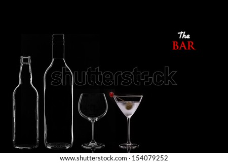 Bar Concept with a Beer Bottle, a Wine Bottle, a Wine Glass and a Cocktail in a Martini Glass on a Black Background. Copy Space. - stock photo