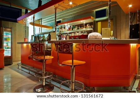 Bar counter and barstools  in empty cafe-bar with orange interior - stock photo