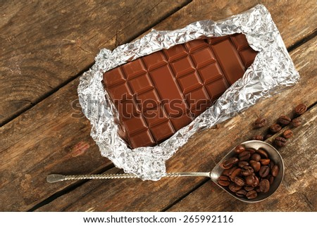 Bar of chocolate in foil with coffee beans in spoon on wooden background - stock photo