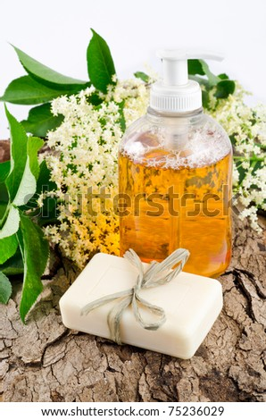bar of soap and liquid cleanser with elderberry flowers - stock photo