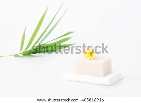 Bar of soap with frangipani flower and bamboo leaf in the background - stock photo