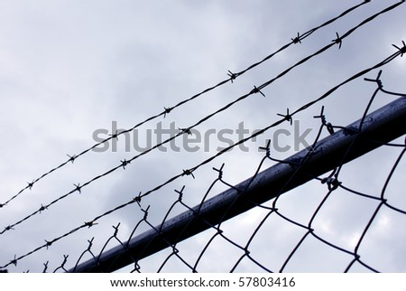 Barb wire against stormy sky - stock photo