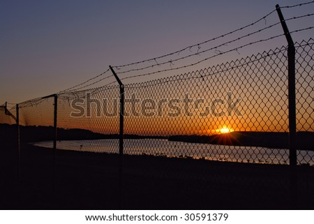 Barb wire on top of chain link fence at the border near a river at sunset