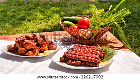 barbecue and grilled sausages with tomato and cucumber - stock photo