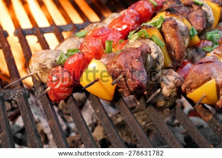 Barbecue Beef Kebabs On The Hot Grill Close-up. Flames of Fire In The Background - stock photo