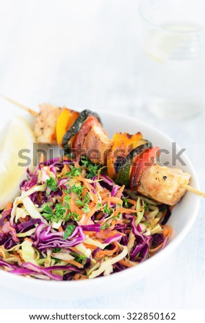 Barbecue chicken kebabs on wooden skewer sticks served with raw side salad coleslaw made of shredded cabbage and carrot - stock photo