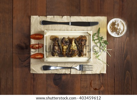 Barbecue chicken legs and chicken wings with arugula, cherry tomatoes and a glass of beer. Serving Table. top view closeup