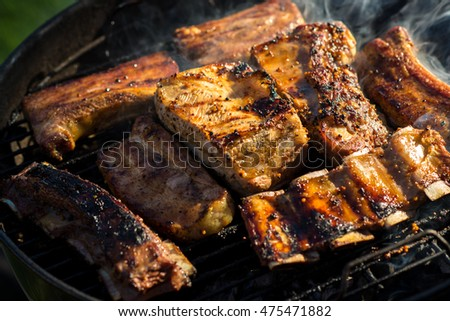 Barbecue grill concept. Assorted delicious grilled meat with corn over the coals on a barbecue
