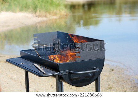 Barbecue grill on beach of river - stock photo