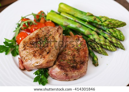 Barbecue grilled beef steak meat with asparagus and tomatoes. - stock photo