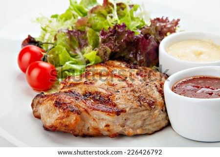 Barbecue grilled steak meat with vegetables and sauces. - stock photo