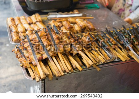 """Barbecue meat - the ingredient of """"bun cha"""" is the famous Vietnamese noodle soup with bbq meat, spring roll, vermicelli and fresh vegetable served on bamboo flat basket - stock photo"""