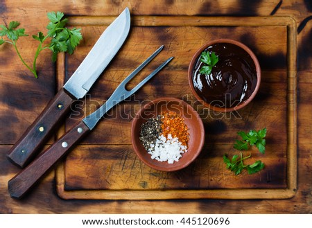 Barbecue sauce, salt, red and black pepper in clay bowls, meat fork, knife and napkin on wooden cutting board. Top view. - stock photo
