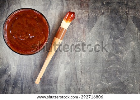 Barbecue sauce with basting brush over stone table with room for copy space.  - stock photo
