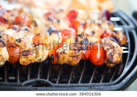 Barbecue skewers being grilled on a bright summer day, close up with shallow focus  - stock photo